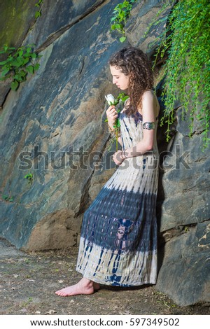 Lonely American teenager girl with curly hair, wearing patterned long dress, bracelet, barefoot, stands against rocks at Central Park, New York, holding white rose, looking down.