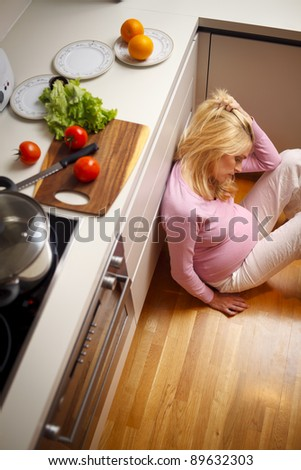 Lonely and depressed pregnant women sitting on the kitchen floor. - stock photo