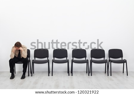 Lonely and desperate businessman sitting on a chair - stress concept - stock photo