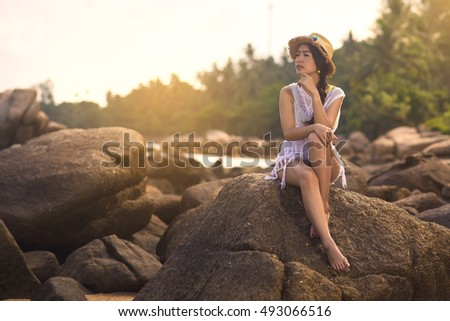 lonely asian young girl wear hat sitting alone on rock in sea beach with sun light