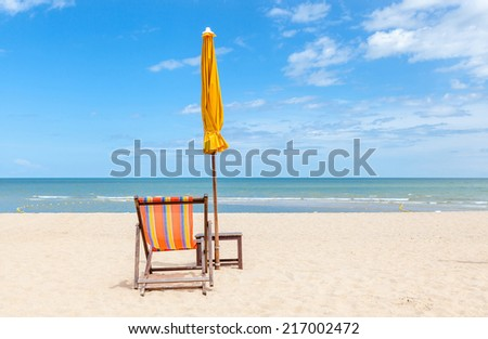 Lonely beach chair and closed sun umbrella on beautiful beach. Concept for rest, relaxation and holiday. - stock photo