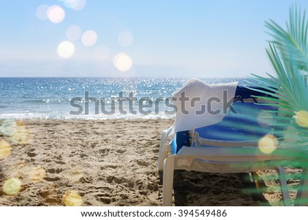 Lonely beach chair with hat at beach, summer holiday concept. - stock photo