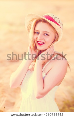 Lonely beautiful young blonde Scottish girl in white dress with straw hat posing at golden wheat field expressing calmness emotions. Vintage retro style effect - stock photo