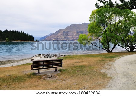 lonely bench by the lake - nobody outdoor park day concept tranquil empty lonely scenery nature - stock photo