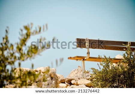 Lonely bench on the white rocks. Greece - stock photo