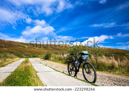 Lonely bicycle in sunny mountain landscape. Green grass, blue sky - stock photo