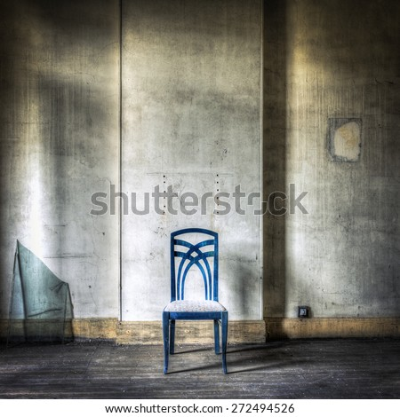 Lonely blue chair in a grungy interior - stock photo