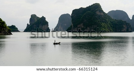 Lonely boat drifts through calm Halong Bay islands, Vietnam,Asia - stock photo