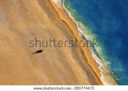 Lonely boat on a beach with aerial view. - stock photo