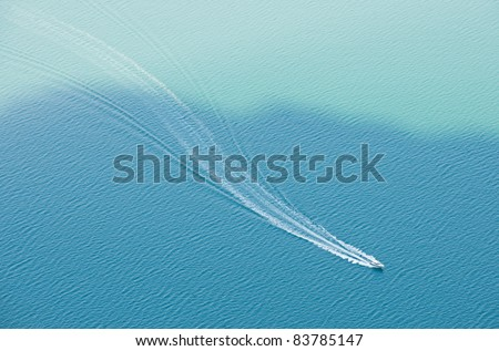 lonely boat on the blue water - stock photo