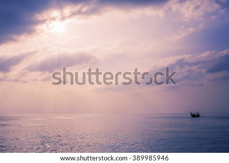 Lonely boat under sun rays at sunset in gorgeous Maya bay, Phi-Phi, Thailand. Image with selective focus and toning - stock photo