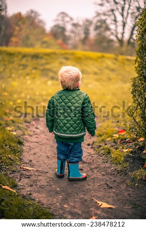 Lonely boy in a garden at autumn