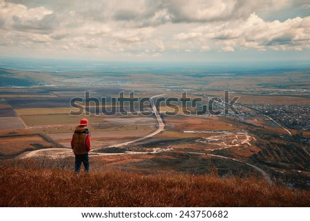 Lonely boy on a background of the valley - stock photo