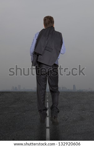 Lonely businessman is on the road against the background of stormy skies - stock photo