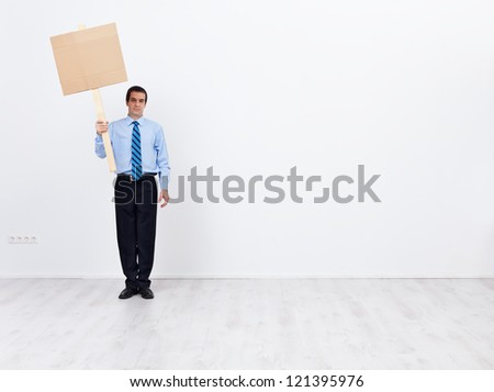 Lonely businessman with blank sign placard and lots of copy space - stock photo