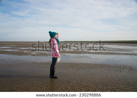 lonely child during mudflat hiking tour in northern sea - stock photo