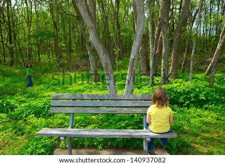 Lonely children sad looking the forest girl sitting at the park bench - stock photo