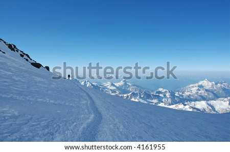 Lonely climber over the mountain peaks ascending the Elbrus, highest peak in Russia, Caucasus. - stock photo