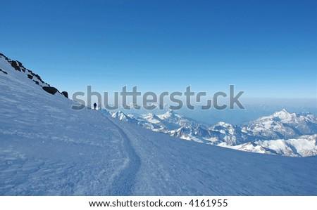 Lonely climber over the mountain peaks ascending the Elbrus, highest peak in Russia, Caucasus. - stock photo