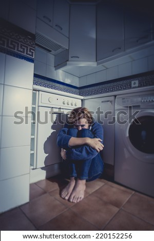 lonely depressed and sick woman sitting alone on kitchen floor in stress , depression and sadness feeling miserable in barefoot looking desperate hugging or holding her knees - stock photo