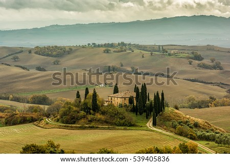Lonely farmhouse with golden meadow hills. Tuscan autumn landscape. Tuscan Villa on countryside, San Quirico d'Orcia, Tuscany, Italy. Horizontal composition.