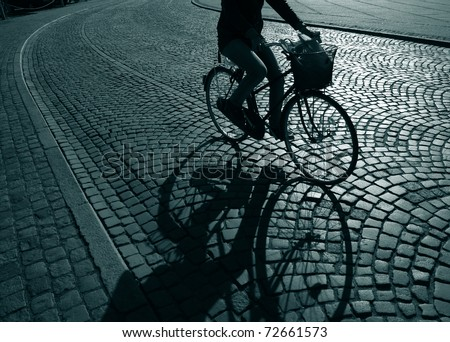 Lonely female cyclist on her way home from work - Denmark. - stock photo