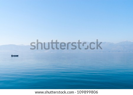 Lonely fisher in the sea near Nafplio, Greece - stock photo