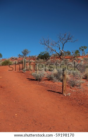 Lonely footpath through the typical red sand desert of Central Australia - stock photo