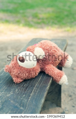 Lonely forgotten teddy bear toy lying on the bench. Awaiting for owner. - stock photo