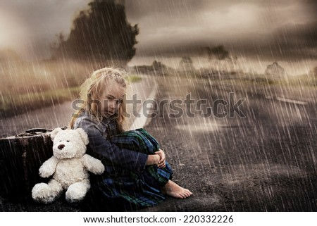 Lonely girl alone on the street on a rainy day - stock photo