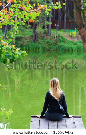 Lonely girl by the lake in the park sitting on a bridge - stock photo