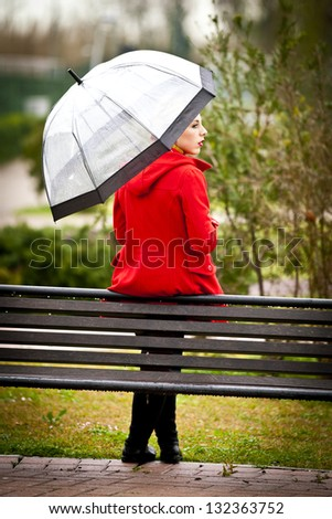 Lonely girl in a park in a rainy day with umbrella - stock photo