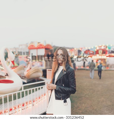 Lonely girl in the leather jacket is in the evening in the amusement park
