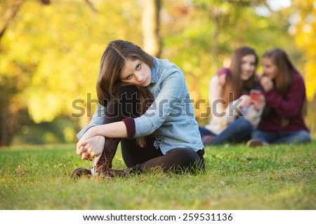 Lonely girl leaning on knee in front of teenagers talking - stock photo