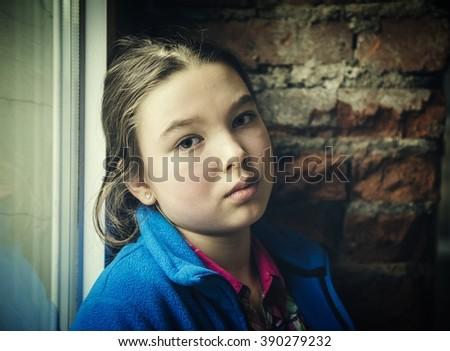 Lonely girl near window thinking about something. LOMO effect - stock photo