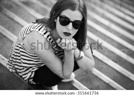 Lonely girl on the stairs. Black and white image - stock photo