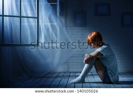 Lonely girl sits in an empty dark room opposite the window - stock photo