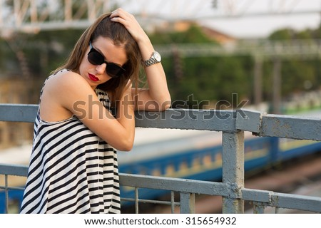 Lonely girl standing on the bridge. Toned image - stock photo