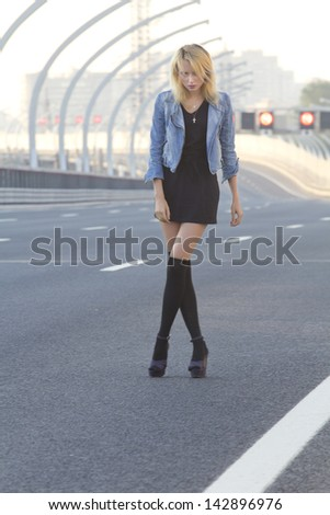 Lonely girl standing on the highway in St. Petersburg, Russia.
