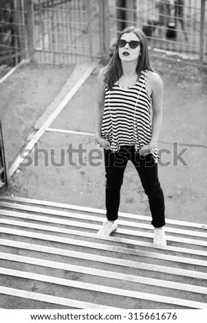 Lonely girl standing on the stairs. Black and white image - stock photo