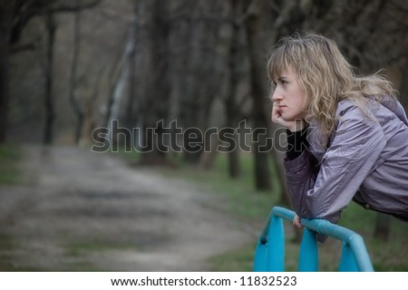 Lonely girl thinks about something sad in park - stock photo