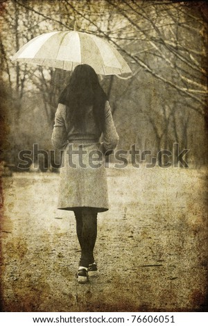 Lonely girl walking at alley in the park in rainy day. Photo in image style. - stock photo