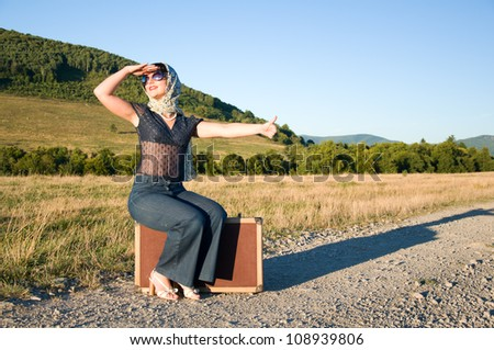Lonely girl with suitcase at country road. - stock photo
