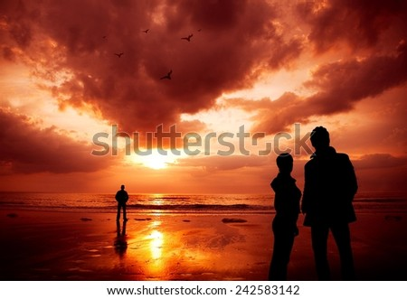 Lonely guy watching a sunset, couple behind him - intentionally saturated for dramatic look