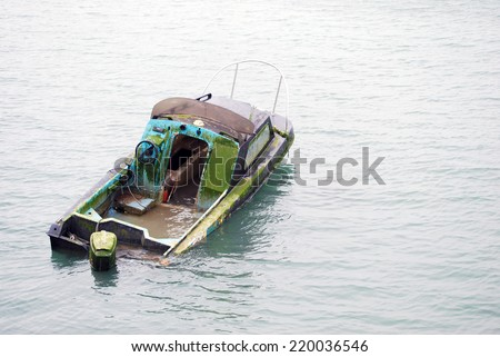 Lonely half sunk abandoned boat in middle of river - stock photo