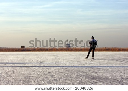 Lonely ice skater on a cold winter in the countryside on frozen ice in the Netherlands - stock photo