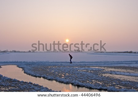 Lonely iceskater at sunset in the countryside from the Netherlands in winter - stock photo