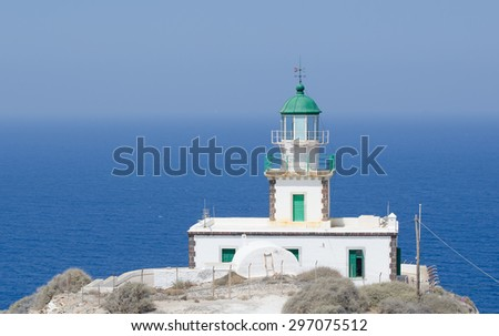 Lonely lighthouse stands on a cliff top in the archipelago of Santorini Greece - stock photo
