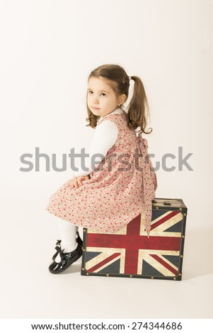 Lonely little girl sitting on a old suitcase and waiting, studio shot on white background - stock photo
