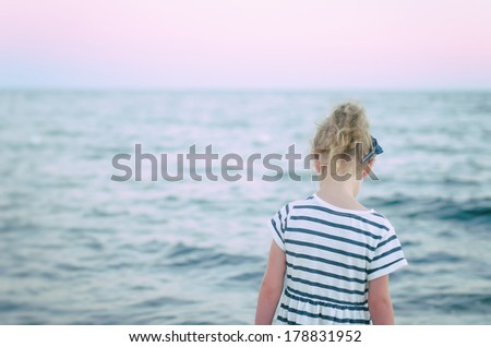 Lonely little girl. View from the back. - stock photo